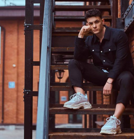 A young pensive guy sitting on stairs outside